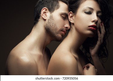 Emotive portrait of two lovers over chocolate background - handsome man and gorgeous woman with perfect hair and skin. Pure passion. Close up. Studio shot