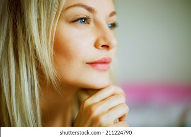Emotive portrait of young beautiful woman with long blond hair. Close up