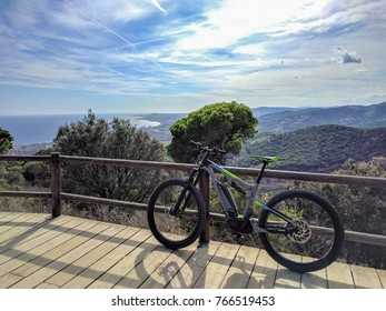 E-Mountainbike leaning against handrail on top of mountain