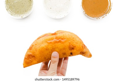 Empanada creative layout on a white background. Venezuelan and Colombian instagram food composition. Top view, flat lay. Fried empanadas from America with different sauces to dip