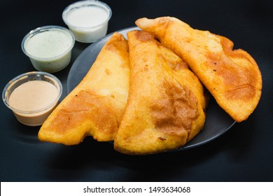 Empanadas venezolanas on a black background with different sauces like guasacaca and spicy sauce. Empanada from Venezuela is fried and made with maize.