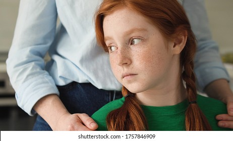 Emphatic woman calming and supporting upset ginger girl, bullying at school