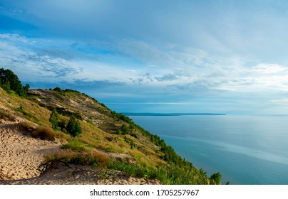 Empire Bluffs Scenic Lookout Facing Platte Bay in Sleeping Bear Dunes National Lakeshore on hot, sunny, and bright summer day. Great spot for hiking in swimming. Bright green vegetation in the dunes.
