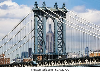 Empire State Building framed within the archway of Manhattan Bridge