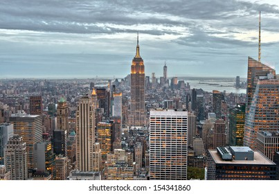 Empire State and Manhattan buildings with lights on  from a high view, in the dusk of New York City, USA.