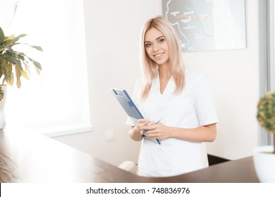 An employee of a beauty salon poses in the reception of a modern beauty salon. She smiles and holds a paper tablet in her hands. She is smiling and posing for a photo.