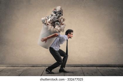 Employee carrying a huge trash bin