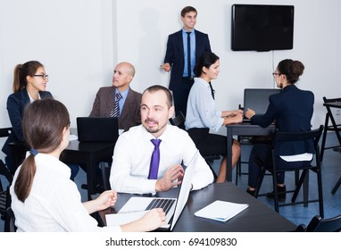 Employee in charge presenting report at business meeting in office