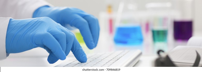 Employee chemical laboratory teacher chemist knocks his fingers keyboard makes notes electronic journal records the analysis data from reactions examining test tubes with the substance arm in gloves