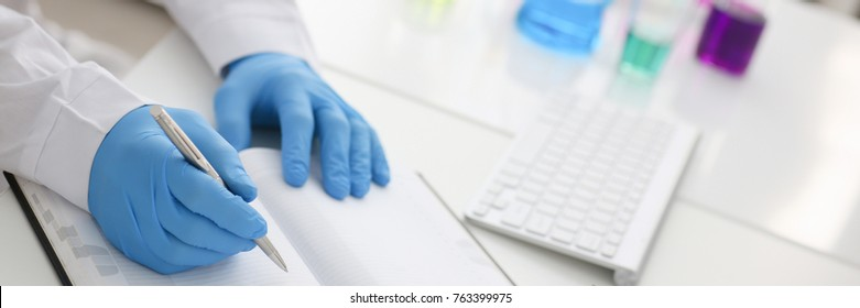 Employee of the chemical laboratory teacher chemist holds a silvery pen in his hand makes notes in the diary records test data from reactions examining test tubes with the substance arm in gloves.