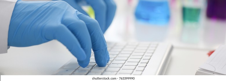 Employee chemical laboratory teacher chemist knocks his fingers keyboard makes notes electronic journal records the analysis data from reactions examining test tubes with the substance arm in gloves.