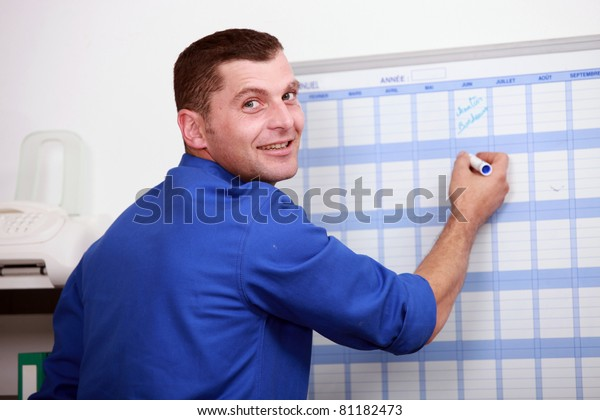 an employee dressed in blue jumpsuit is writing on a calendar