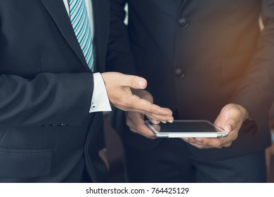 employee explaining project via touchpad to boss and ask for advice.