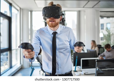 Employee in formal wear trying out VR technology in office. In b