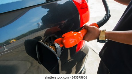 Employee is fueling into tank of the car, Hand holding fuel nozzle