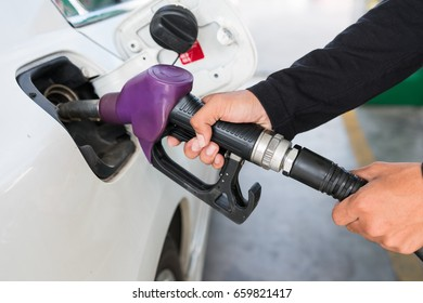 Employee are fueling pump at the gas station. Closed-up of hand.