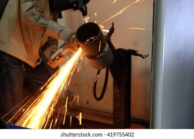 employee grinder steel in workshop (blur background)