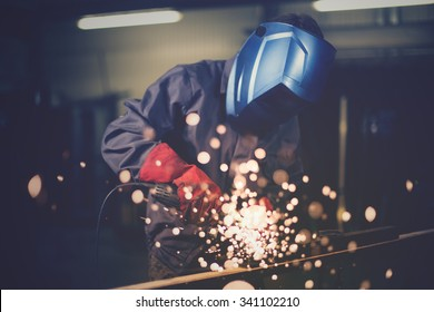 Employee grinding steel with sparks - focus on grinder.
