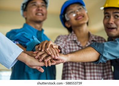 employee group from asian factory make hand shake. manager and worker meeting to good factory performance. the worker is importance for factory.the factory unshaken because employee have good relation