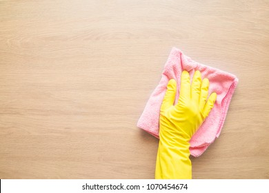 Employee hand in rubber protective glove with microfiber rag wiping wooden table, wall or floor surface in room, bathroom, kitchen. Spring or regular cleanup. Commercial cleaning company concept.