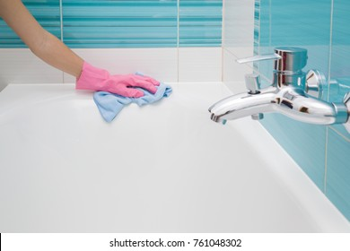 Employee hand in rubber protective glove with rag washing and polishing a bathtub. Maid or housewife cares about house. Spring general or regular clean up. Commercial cleaning company concept.