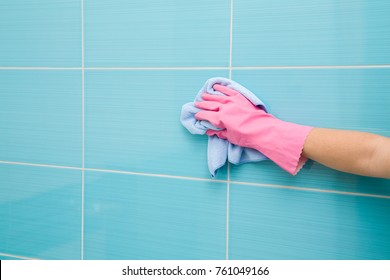 Employee hand in rubber protective glove with micro fiber cloth washing a ceramic tiles from dust in the bathroom. Spring general or regular clean up. Commercial cleaning company concept.