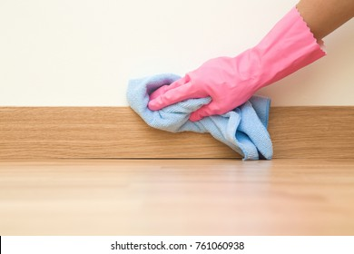Employee hand in rubber protective glove with micro fiber cloth wiping a baseboard on the floor from dust at the wall. Spring general or regular clean up. Commercial cleaning company concept.