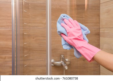 Employee hand in rubber protective glove with rag washing and polishing a glass shower doors. Housewife cares about house. Spring general or regular clean up. Commercial cleaning company concept.