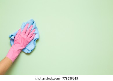 Employee hand in rubber protective glove with micro fiber cloth wiping wall from dust. Maid or housewife cares about house. Spring general or regular clean up. Commercial cleaning company concept.