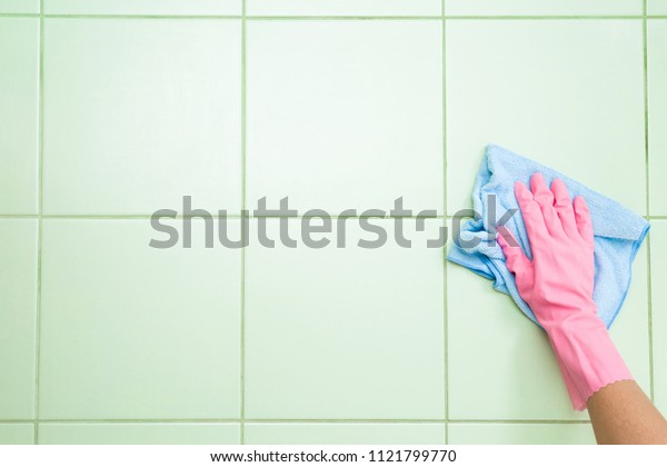 Employee hand in rubber protective glove washing pastel green ceramic tiles with rag. Spring general or regular cleanup. Commercial cleaning company. Service concept. Copy space. Empty place for text.