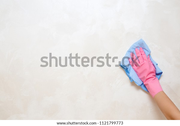 Employee hand in rubber protective glove with rag wiping vintage wall from dust. General or regular cleanup. Commercial cleaning company. Service concept. Copy space. Empty place for text or logo.