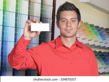 A employee of a hardware store at work holding a white card.