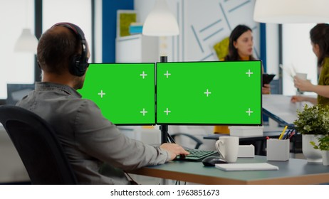Employee with headphones using dual monitror setup with green screen, chroma key mock up isolated display sitting in video production studio. Man ditor processing film montage on pc in creative agency