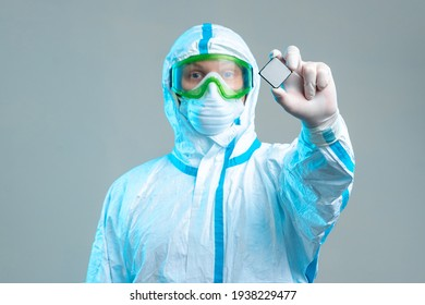 An employee holds a microchip in his hands, stands in a protective suit, glasses, a mask and gloves. Latest technologies, electronic microcircuit, computer security, neural networks