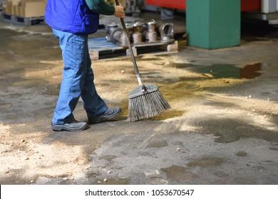 Der Angestellte führt Bodenreinigung in der Fabrik durch. Der Arbeiter fegt Böden in der Fabrik mit speziellem Sand, um Industrieschmutz zu entfernen