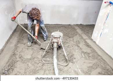 Employee performs sand and cement screed floor. Sand and cement floor screed