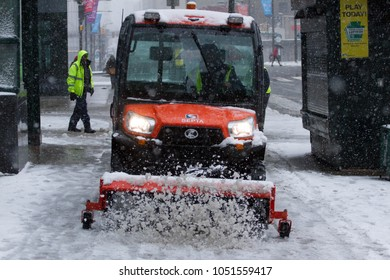 An employee with Philadelphia area transit agency SEPTA clears a sidewalk during a Nor'easter on the first full day of spring, Wednesday, March 21, 2018.