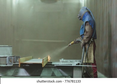 An employee prepares a metal part for painting. A harsh man works in the factory. Sandblast. Blast it.