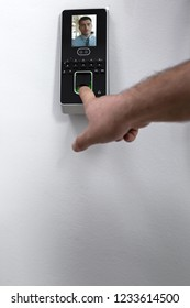 Employee scanning fingerprint record hours work time.
