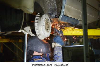 the employee of the service station produces body repair with a welding machine in hand. sparks from welding machine. car service, car repair