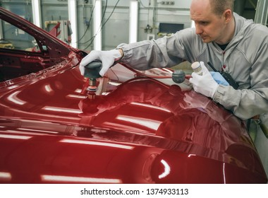 The employee of the shop paint the body of the car, sanding the painted part of a pneumatic tool