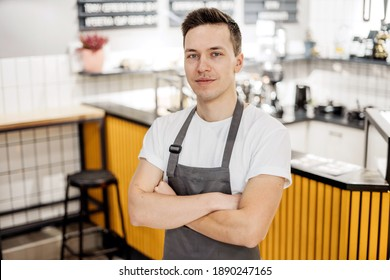 the employee of the staff of restaurant cafe bartender with dark hair. a man of Caucasian appearance in a work apron and a white T-shirt. at work posing looking at the camera. Stylish place