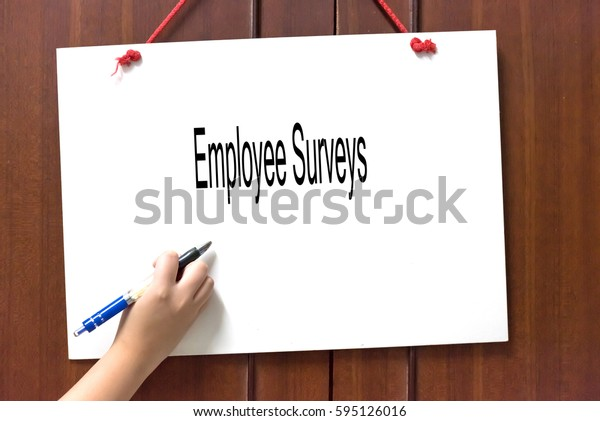 Employee Surveys -  Hand writing word to represent the meaning of Business word as concept.
