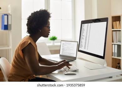 Employee using office computer. African-American woman sitting at desk, looking at desktop PC screen, doing research, studying data reports, working with business documents and online spreadsheets