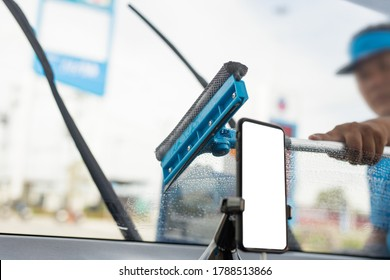 Employee using sponge to clean a car windscreen at gas station