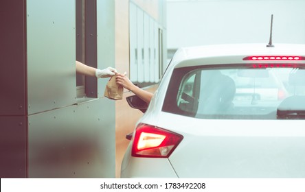 Employee wearing gloves delivers take out food out the window. Shopping for food from the car. Pick up fast food from the counter. Concept of social distance and new normality.