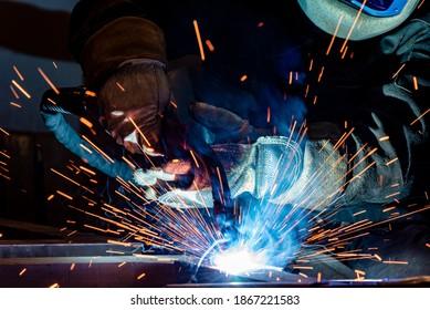 Angestellter Schweißstahl mit Funken unter Verwendung von Mag-Magnet Schweißer - Fokus auf Funken. Schweißmetall