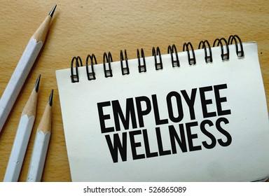 Employee Wellness text written on a notebook with pencils