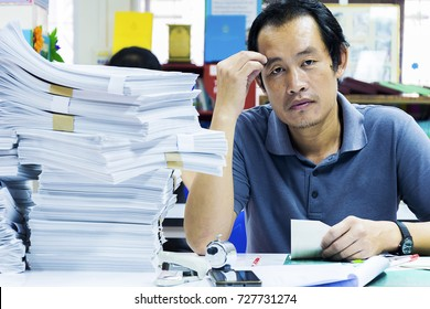 An employee who works hard with a large amount of documents, salaryman stressed by a lot of work, his desk is full of disorganized things.