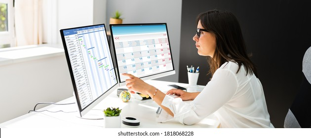Employee Working On Calendar Schedule And Staff Time Sheet